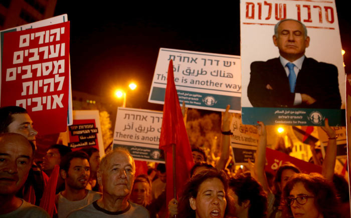 """Israeli Jews and Arabs march together in downtown Jerusalem on 17 October 2015, during a left wing protest against the ongoing situation. The placard on the right bearing a portrait of Israeli Prime Minister Benyamin Netanyahu reads in Hebrew """"Refuser of peace"""" and the red placard on the left reads in Hebrew """"Jews and Arabs refuse to be enemies"""". Picture: AFP"""