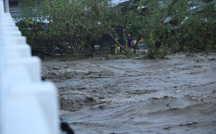 People watch a swollen river due to heavy rains brought by Super Typhoon Goni in Legazpi City, Philippines' Abay province on 1 November 2020. Picture: AFP.