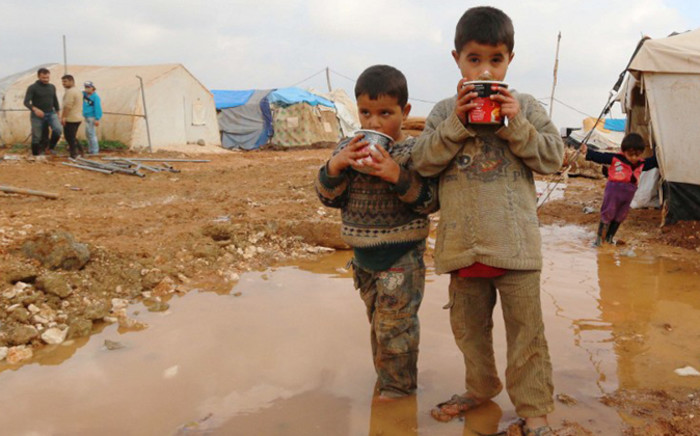 FILE: Displaced Syrian children stand in muddy water after heavy rains in the Bab Al-Salama camp for people fleeing the violence in Syria on 11 December, 2014, on the border with Turkey. Picture: AFP