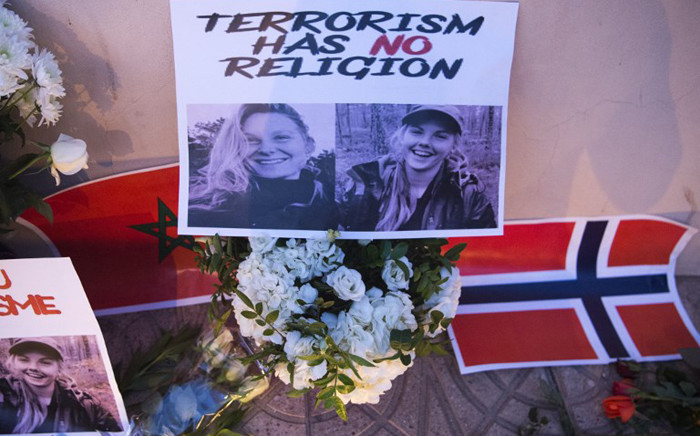 This picture taken on 21 December 2018 shows a combo photo murdered Danish student Louisa Vesterager Jespersen (L) and Nowegian Maren Ueland placed on top of flowers and between the flags of Morocco and Norway as Moroccans pay tribute to the Scandinavian victims. Picture: AFP.