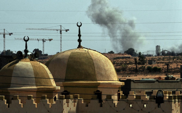 FILE: Smoke rises behind a mosque as NATO planes bombard troop positions close to the eastern gate of the city of Sirte. Picture: AFP