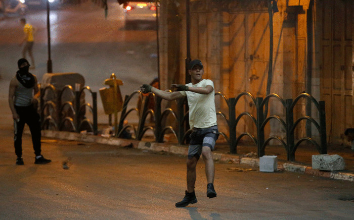 A Palestinian youth throws stones during clashes with Israeli security forces in the city center of the occupied West Bank town of Hebron on April 25, 2021, following a protest in support of Palestinian demonstration in Israeli-annexed east Jerusalem. Picture: Hazem Bader / AFP.