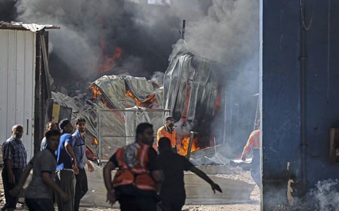 Palestinian firefighters rush to extinguish a huge fire at the Foamco mattress factory east of Jabalia in the northern Gaza Strip, on 17 May 2021, after Israeli airstrikes. Picture: MAHMUD HAMS/AFP