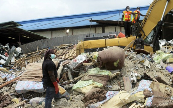 Rescue workers clear away mattresses used by occupants of the collapsed guesthouse of the Synagogue Church of All Nations (SCOAN) at Ikotun in Lagos on 17 September, 2014. Picture: AFP.