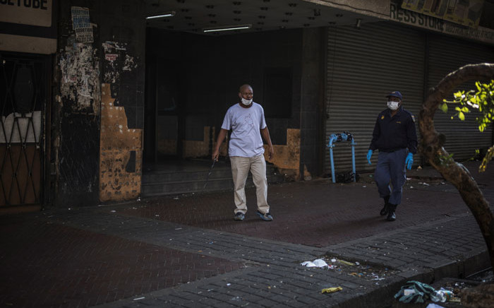 A plain clothed South African policeman carries a whip while he and an uniformed colleague try to clear a pavement in Hillbrow, Johannesburg, on 27 March 2020 in an effort to enforce distancing. Picture: AFP