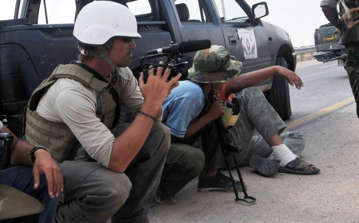 A photo taken on 29 September 2011 shows US freelance reporter James Foley (L) on the highway between the airport and the West Gate of Sirte, Libya. Picture: AFP.