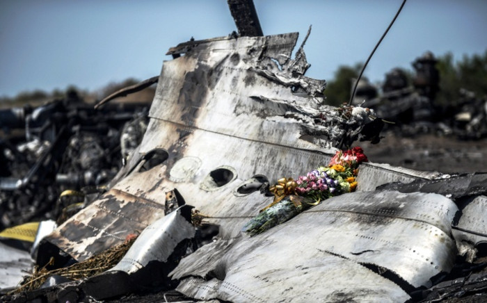 This photo taken on 26 July 2014 shows flowers, left by parents of an Australian victim of the crash, laid on a piece of the Malaysia Airlines plane MH17, near the village of Hrabove in the Donetsk region. Picture: AFP.