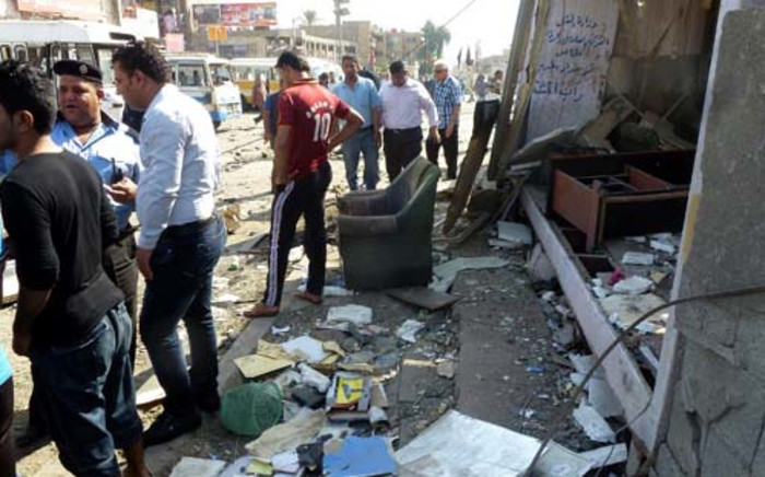 Iraqis gather at the scene of an explosion at a small bus station. Picture: AFP