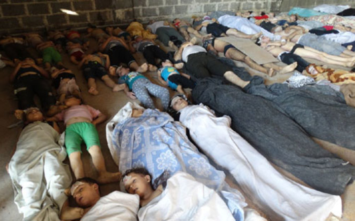 A handout image released by the Syrian opposition's Shaam News Network shows people inspecting bodies of children and adults laying on the ground as Syrian rebels claim they were killed in a toxic gas attack by pro-government forces in eastern Ghouta, on the outskirts of Damascus on August 21, 2013. Picture: AFP