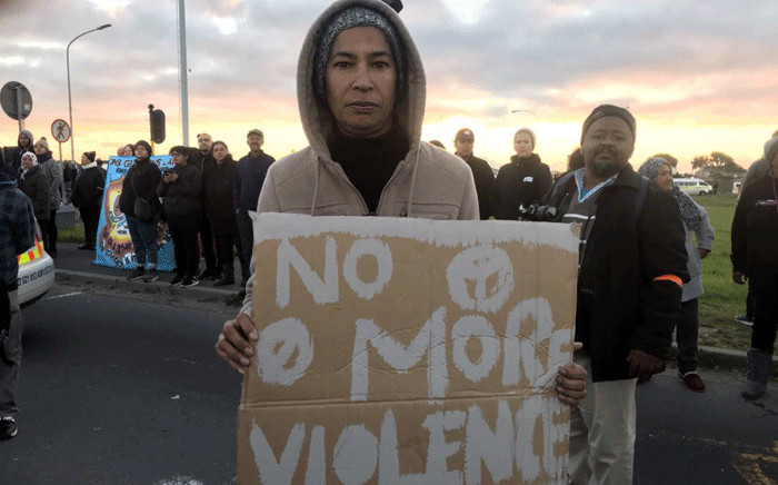 FILE: A Bonteheuwel resident stands with a placard during a protest against gang violence on 29 August 2018. Picture: Shamiela Fisher/EWN.