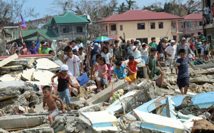 Residents walk through debris as they rush to a rescue helicopter delivering relief foods in Hernani town, Eastern Samar province, central Philippines on 11 November. Picture:AFP.