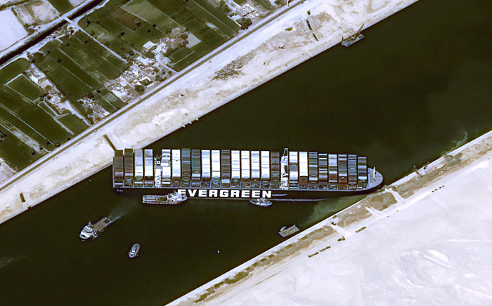 This handout satellite image courtesy of Cnes 2021 released on March 25, 2021 by Airbus DS shows the Taiwan-owned MV 'Ever Given' (Evergreen) container ship, a 400-metre- (1,300-foot-)long and 59-metre wide vessel, lodged sideways and impeding all traffic across the waterway of Egypt's Suez Canal. Picture: Distribution Airbus DS / AFP.