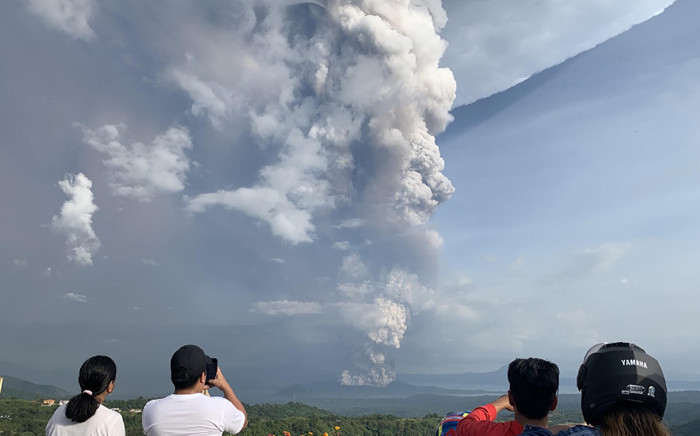 People take photos of a phreatic explosion from the Taal volcano as seen from the town of Tagaytay in Cavite province, southwest of Manila, on 12 January 2020. Picture: AFP