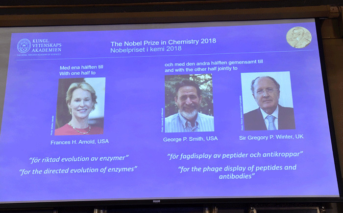 A screen displays portraits of Frances H Arnold of the United States, George P Smith of the United States and Gregory P Winter of Great Britain during the announcement of the winners of the 2018 Nobel Prize in Chemestry at the Royal Swedish Academy of Sciences on 3 October 2018 in Stockholm. Picture: AFP.