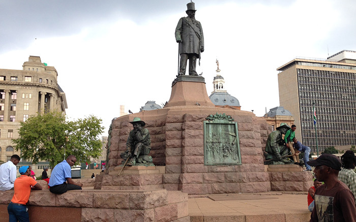 People walk by as the Paul Kruger and the four Burghers statue looms large over Church Square in Pretoria, 31 March 2015. Picture: Vumani Mkhize/EWN.