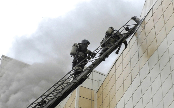 This handout picture released by The Russian Emergency Situations Ministry on 25 March 2018 shows emergency firefighters extinguishing a fire outside a burning shopping centre in Kemerovo. Picture: AFP