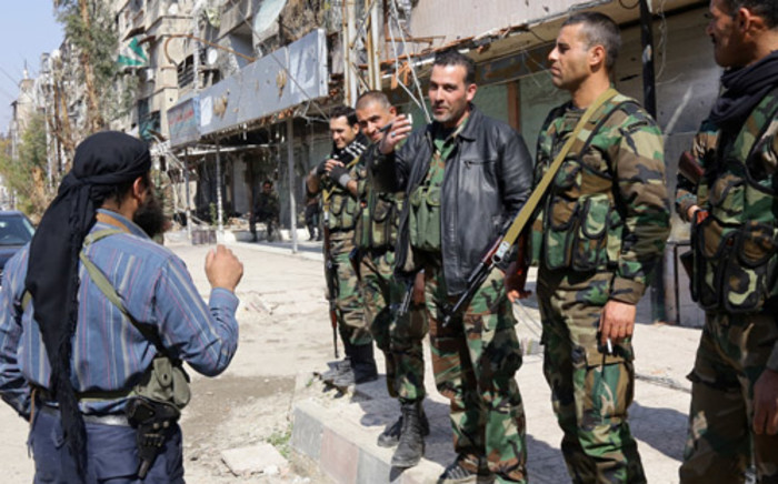 FILE: Pro-regime fighters speak with a rebel fighter in the town of Babbila, a suburb of Damascus, during a cease fire agreement between the group controlling the town and the regime on 17 February, 2014. Picture: AFP.