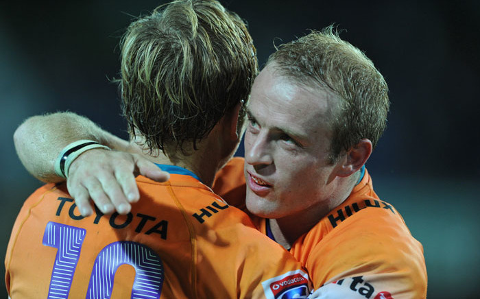 FILE. Cheetahs halfback Sarel Pretorius (R) congratulates teammate Joe Pietersen (L). Picture: AFP/ Greg Wood.