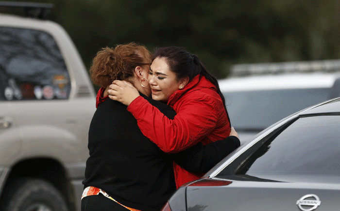 Vanessa Flores (R) embraces another woman after she leaves the locked down Veterans Home of California during an active shooter turned hostage situation on 9 March 2018 in Yountville, California. Picture: AFP.