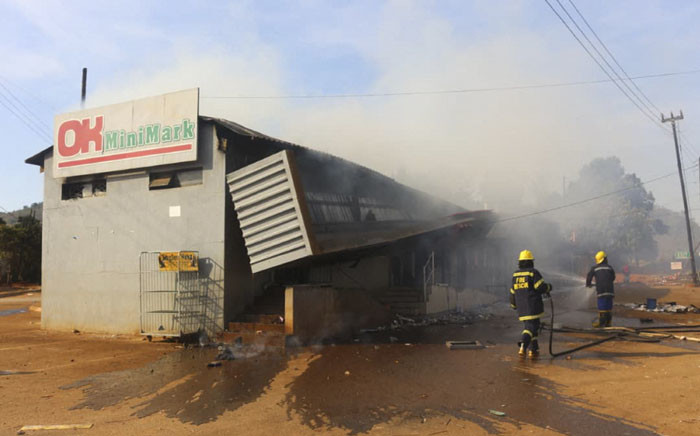 Firefighters extinguish a fire at a supermarket in Manzini, eSwatini, on 30 June 2021. Demonstrations escalated radically in eSwatini as protesters took to the streets demanding immediate political reforms. Picture: AFP