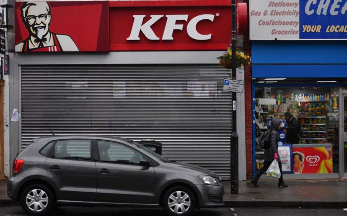 Pedestrians pass outside a closed KFC fast food store in south London on 19 February 2018 as the US fast food chain said it had been forced to close many restaurants in Britain because of a new supplier failing to deliver chicken in time. Picture: AFP
