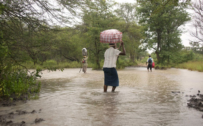 FILE: Villagers carry food and other belongings as they walk across a puddle along a flooded footpath on 4 March 2017 heading towards Sipepa flood victims camp. Picture: AFP
