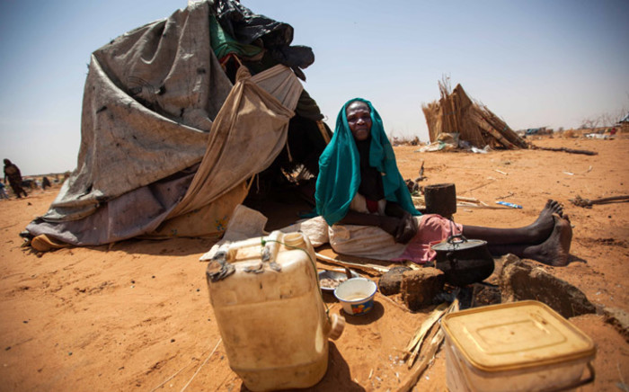 A handout picture released by UNAMID shows Aisha Abdala, a displaced woman from Katila, South Darfur, cooking next to her shelter at the al-Sereif camp for Internally Displaced Persons. Picture: AFP