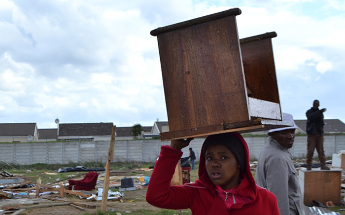 A child carries a table on her head after police dismantled her family's house during a mass eviction in Nomzamo near Strand in Cape Town on 3 June 2014. Picture: Carmel Loggenberg/EWN.