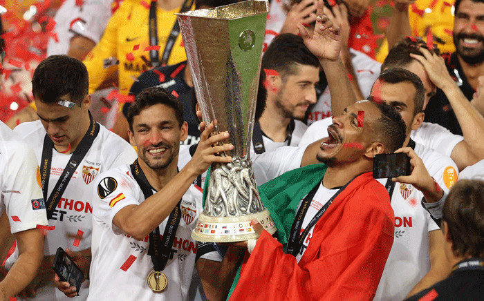 Sevilla's Spanish midfielder Jesus Navas (L) and Sevilla's Brazilian midfielder Fernando (R) hold the trophy as they celebrate after Sevilla won the UEFA Europa League final football match Sevilla v Inter Milan on 21 August 2020, in Cologne, western Germany. Picture: AFP