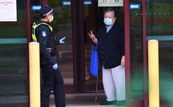 Police speak to a resident at the entrance of one of nine public housing estates locked down due to a spike in COVID-19 coronavirus numbers in Melbourne on 6 July 2020. Picture: AFP