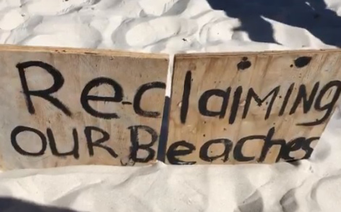 """A """"Reclaiming Our Beaches"""" board is erected at Clifton 4th Beach in Cape Town during a sit-in by activists. Picture: EWN."""