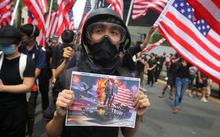 A man holds a placard as protesters wave US national flags while they march from Chater Garden to the US consulate in Hong Kong on 8 September 2019, to call on the US to pressure Beijing to meet their demands and for Congress to pass a recently proposed bill that expresses support for the protest movement. Pro-democracy activists planned to rally outside the US consulate in Hong Kong on 8 September as they try to keep international pressure on Beijing following three months of huge, sometimes violent, protests. Picture: AFP