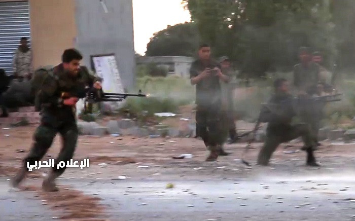 This grab obtained from a video published on the Libyan strongman Khalifa Haftar's self-proclaimed Libyan National Army War Information Division's Facebook page on 16 April 2019, shows a fighter running while firing a machine gun reportedly in a southern suburb of the capital Tripoli. Picture: AFP