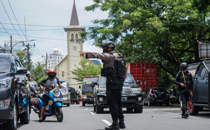 An Indonesian policeman manages the traffic after an explosion outside a church in Makassar on 28 March 2021. Picture: AFP
