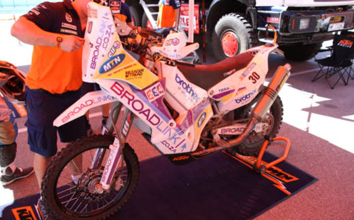 A technician takes a look at Riaan Van Niekerk's motorcycle ahead of another day of competition in the 2014 Dakar Rally. Picture: Derek Alberts/EWN Sport