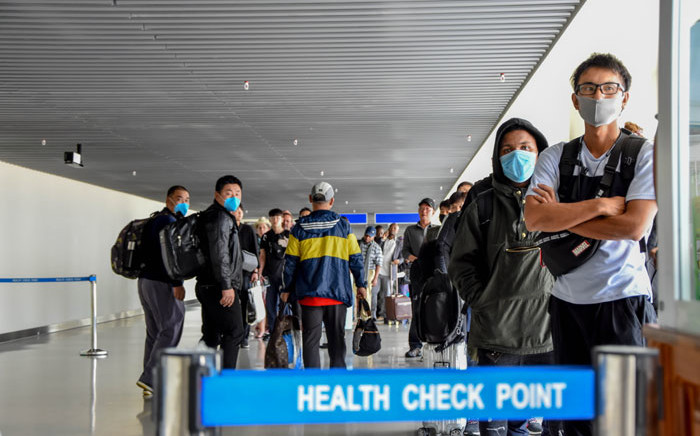 FILE: Passengers arriving from China wait in line to be checked by health officials at the Julius Nyerere International Airport in Dar Es Salaam on 29 January 2020. Picture: AFP