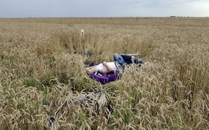 A body lies in a wheat field at the site of the crash of a Malaysia Airlines plane carrying 298 people from Amsterdam to Kuala Lumpur in Grabove, in rebel-held east Ukraine, on 19 July, 2014.
