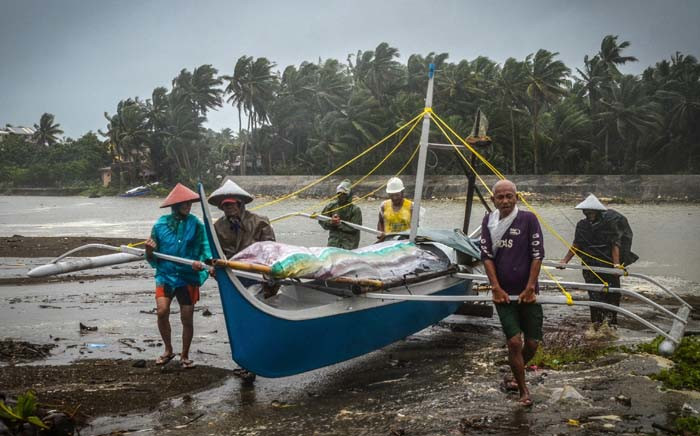Fishermen carry a boat to higher ground in Baybay, eastern Samar on 24 December 2019, after typhoon Phanfone hit the central Philippines. Typhoon Phanfone smashed into the central Philippines on 24 December ruining Christmas plans as thousands were left stranded at ports or told to leave their homes. Picture: AFP.