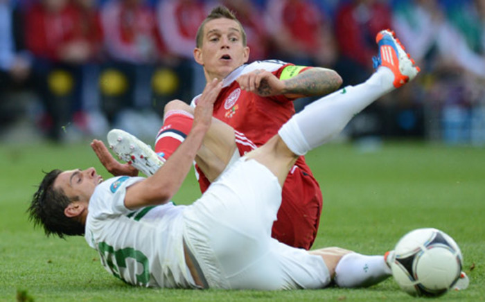 Portuguese forward Helder Postiga (bottom) vies with Danish defender and captain Daniel Agger during the Euro 2012 championships football match Denmark vs Portugal on 13 June 2012. Picture: AFP
