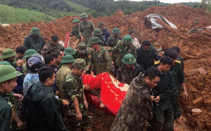 This picture taken on October 18, 2020 and released by the Vietnam News Agency shows military personnel carrying a body recovered from the site of a landslide in central Vietnam's Quang Tri province. Picture: AFP
