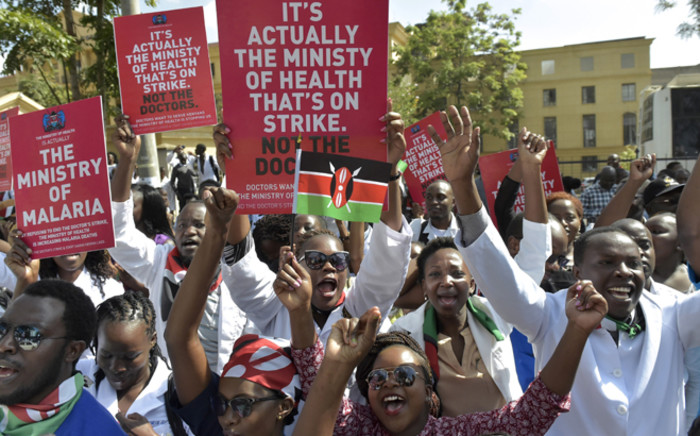 FILE: Kenyan doctors shout slogans and hold placards outside a Nairobi court on 26 January 2017 as they awaited for their union officials to come out. Picture: AFP.