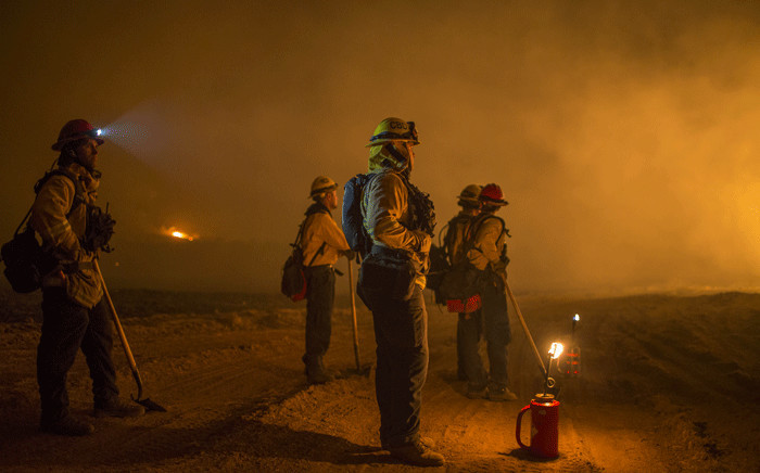 Firefighters set a backfire to make progress against the Thomas Fire before the winds return with the daylight near Lake Casitas on 9 December 2017 near Ojai, California. Picture: AFP