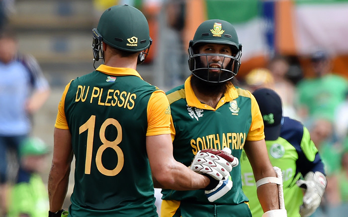 South Africa's Hashim Amla and teammate Faf du Plessis celebrate their combined century during the 2015 Cricket World Cup Pool B match between Ireland and South Africa in Canberra on 3 March, 2015. Picture: AFP.
