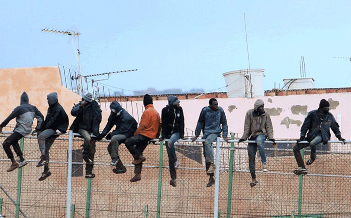 In this file photo taken on 19 February, 2015 migrants sit atop a border fence separating Morocco from the north African Spanish enclave of Melilla in the first attempt to jump since the camp on Mount Gurugu burned down. Picture: AFP