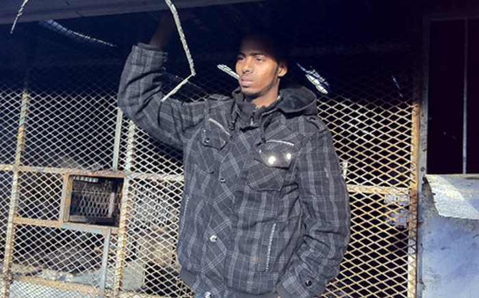 A Somali national stands outside his shop after it was petrol bombed in Mitchells Plain. Picture: Malungelo Booi/EWN