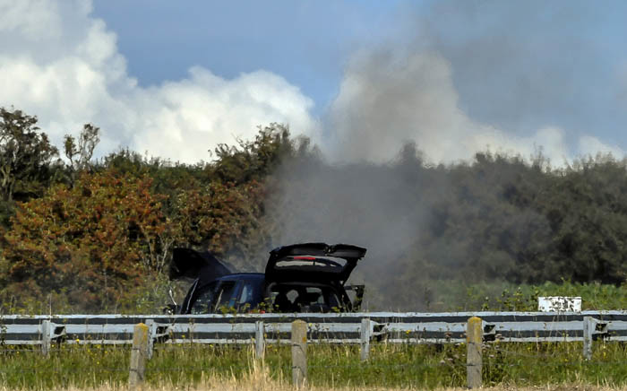 Smoke rises from a damaged BMW car after a controlled explosion as French police inspect the site after they arrested a suspect on the A16 motorway, near Marquise, northern France, on 9 August 2017. Picture: AFP