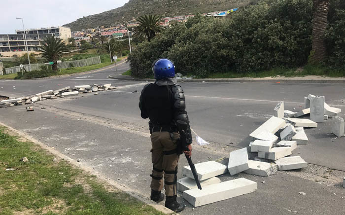 A police officer stands guard on the road in Hangberg during a protest by residents who are reportedly angry at the Agriculture, Forestry and Fisheries Department's decision to cut fishing quotas. Picture: Shamiela Fisher/EWN.