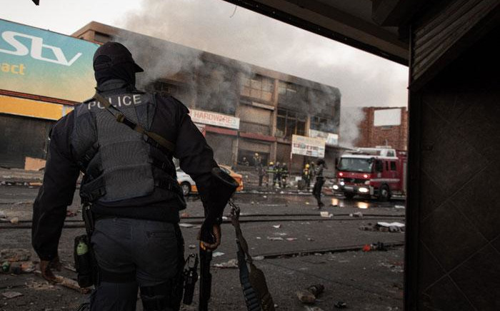 A police officer watches firefighters extinguish a building following riots in Alexandra on 12 July 2021. Picture: Boikhutso Ntsoko/Eyewitness News