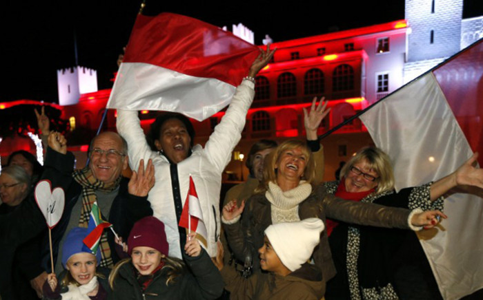 People celebrate in front of the Palace of Monaco as they celebrate the birth oftwins to Prince Albert II and Princess Charlene of Monaco on 10 December, 2014 in Monaco. Picture: AFP.