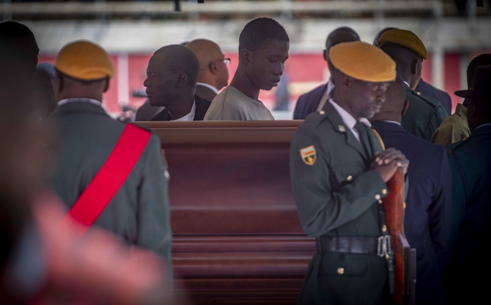 Under heavy police presence after the stampede the day before, mourners at the Rufaro Stadium in Harare queue to see the late former President Robert Mugabe as he lies in his coffin. Picture: Thomas Holder/EWN.